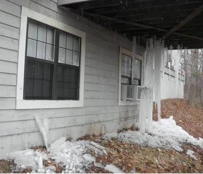 Gray house with large icicles hanging from second story porch