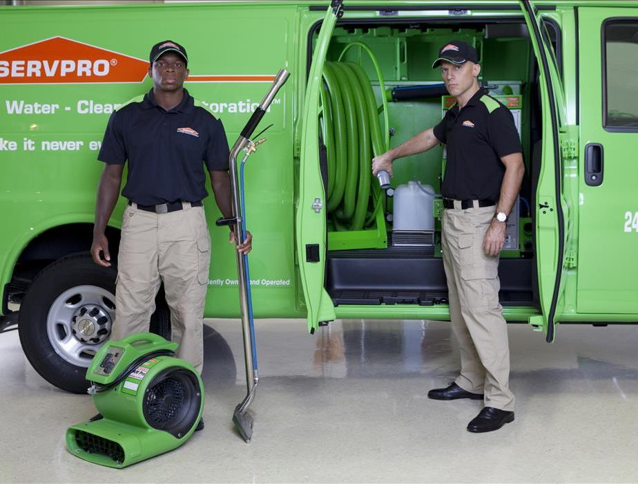 Technicians in front of green SERVPRO Van