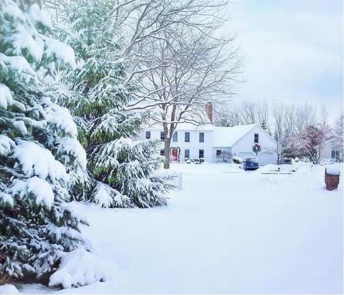 White home in snow with snow covered trees
