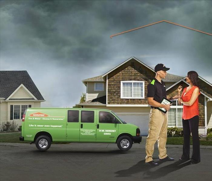 SERVPRO Technician and Customer in front of home